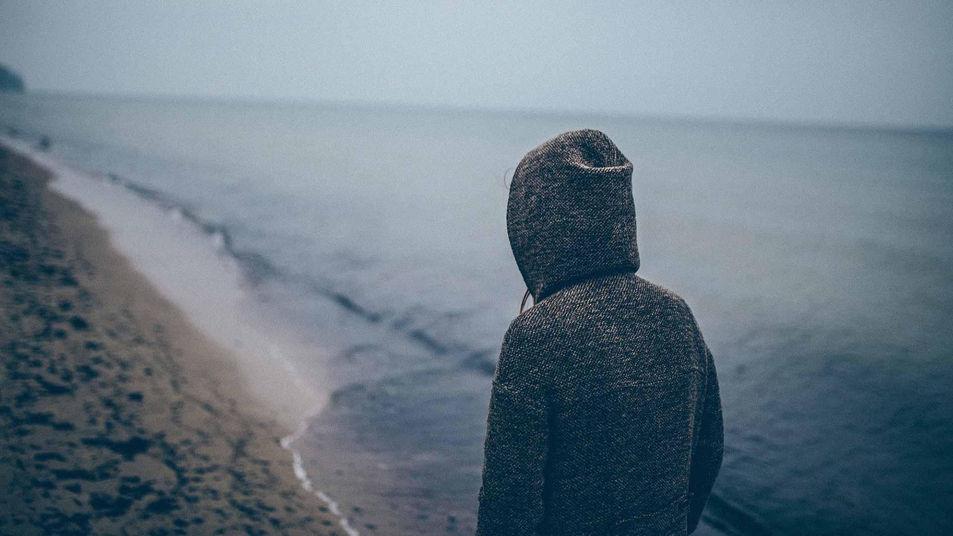 Sad person overlooking ocean alone