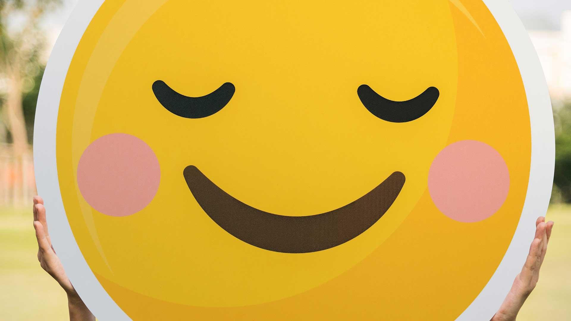 Person holding big happy emoticon