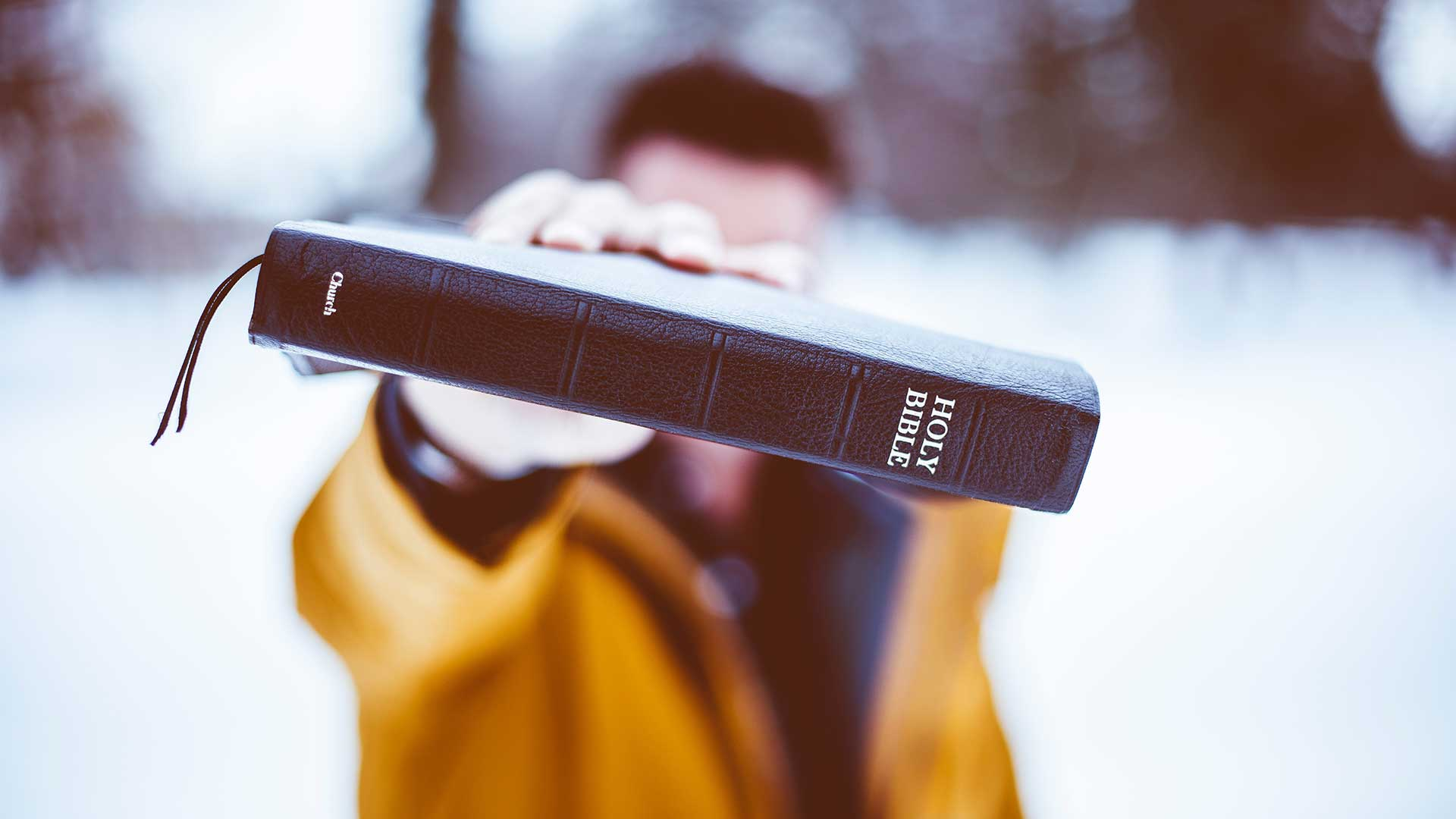 Man holding Bible in face
