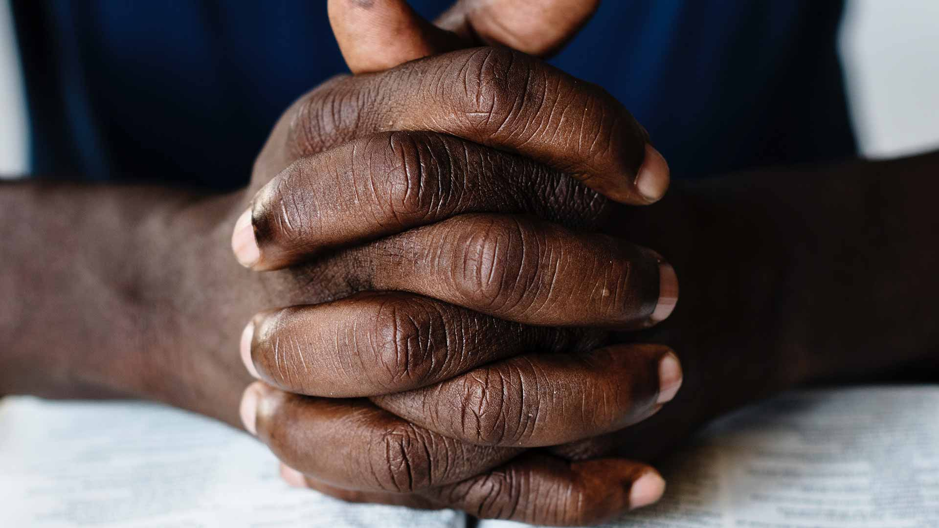 Black man's hands folded in prayer