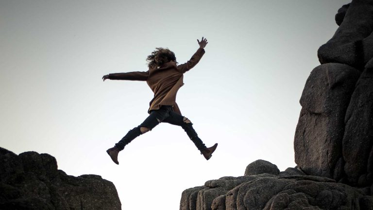 Woman jumping from rock to rock with God's strength