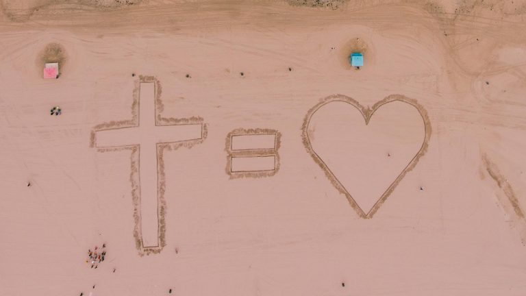 Cross equals love written in the sand